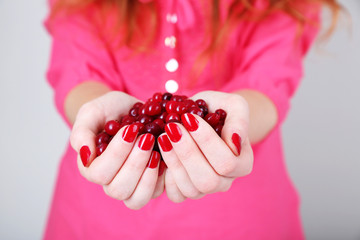 Woman hands holding ripe red cranberries, close up.