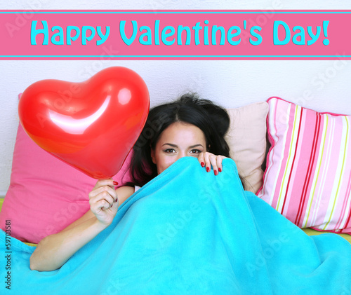 Beautiful woman with balloon in bed on Valentine Day