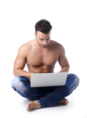 Muscular, shirtless young man on the floor using laptop computer