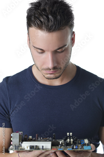 Confused, puzzled computer technician looking at motherboard
