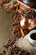 Cup of coffee, pot and grinder on wooden background