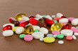 Assortment of pills, tablets and capsules on brown background