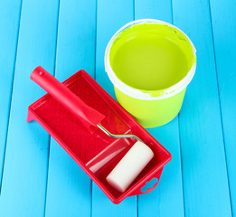 Set for painting: paint pot, paint-roller on blue wooden table