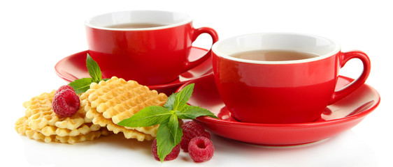Cups of tea with cookies and raspberries isolated on white