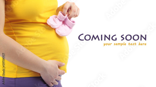 Pregnant woman holding pink baby shoes isolated on white