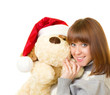 Beautiful young woman in Santa Claus clothes with toy dog