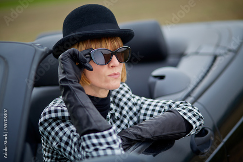 Cool 40s woman with sunglasses in a cabriolet