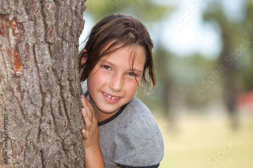 girl looking from behind a tree