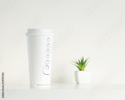 White coffe cup and green potted plant