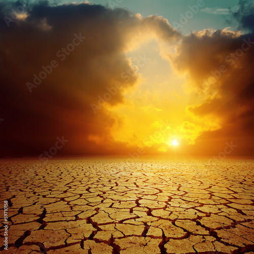 orange cloudy sunset over cracked desert