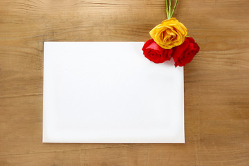 Red and yellow roses on wooden background. Blank sheet of paper,