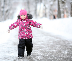 little girl, a child walking in a winter park in snow