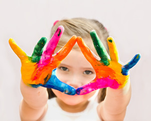Cute little girl with hands in paint