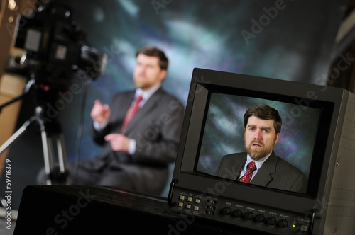 Monitor in production studio showing man talking into a televisi