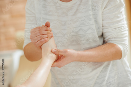 Masseur massaging a child leg