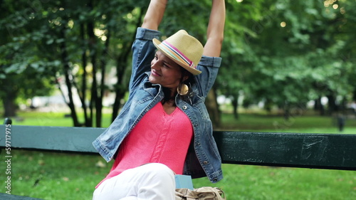 happy woman relaxing and sitting on a bench