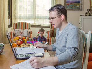 Father working in home office and son playing