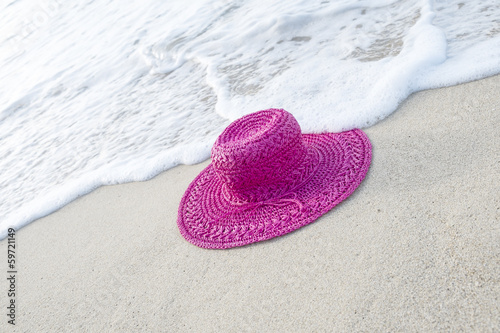 Surf Touching a Pink Straw Hat on a Beach
