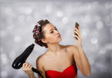 Woman in curlers looking in the phone at light background