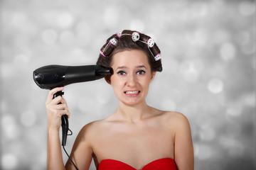 Girl holding a hair dryer as a gun