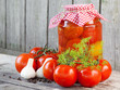 Homemade tomatoes in glass jar. Fresh and canned tomatoes on woo