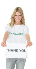 Smiling young female volunteer holding 'thank you' paper