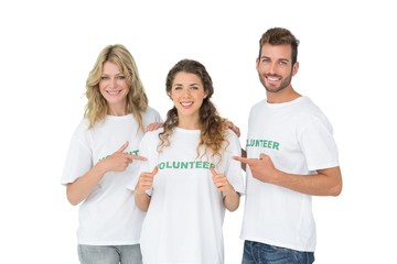 Portrait of happy volunteers pointing to friend