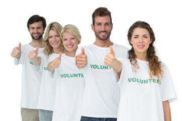Group portrait of happy volunteers gesturing thumbs up
