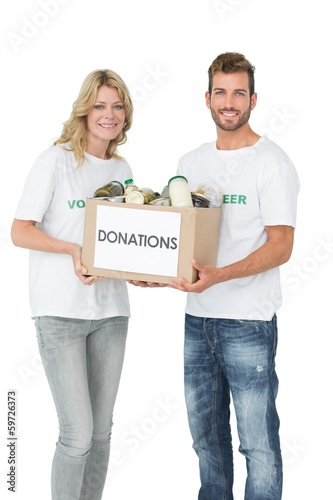 Smiling young couple carrying donation box