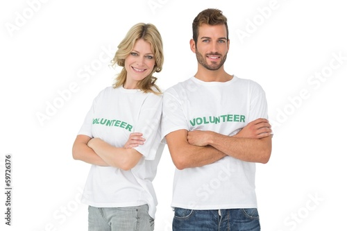 Portrait of two happy volunteers with hands crossed
