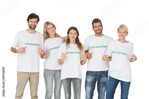 Group portrait of happy volunteers pointing to themselves