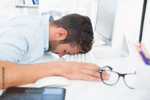 Male artist with head resting on keyboard