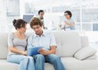 Casual couple using digital tablet with colleagues at creative o