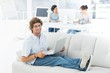 Man using laptop with colleagues in background at creative offic