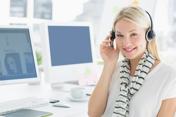 Smiling casual young woman with headset in office
