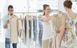 Leinwanddruck Bild - Seller helping shopper choose clothes in store