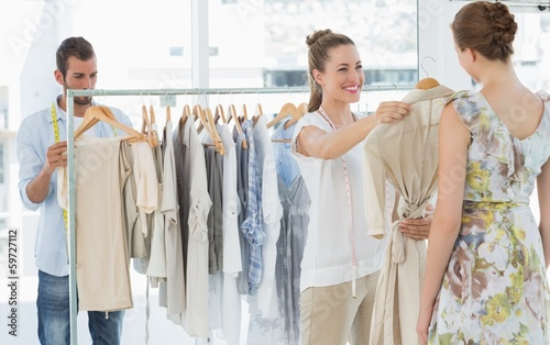 Leinwanddruck Bild Seller helping shopper choose clothes in store