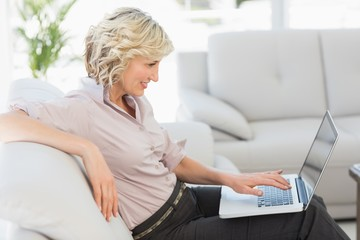 Beautiful businesswoman using laptop in the living room