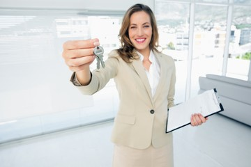 Beautiful happy woman handing over house keys