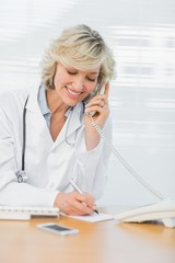 Doctor using phone while writing notes at medical office