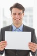 Happy businessman holding blank page