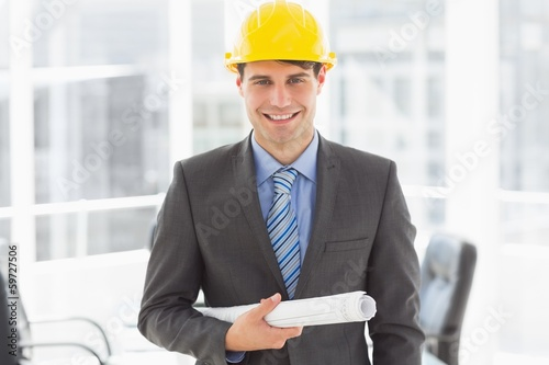 Happy architect holding blueprints smiling at camera