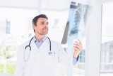 Serious male doctor examining x-ray