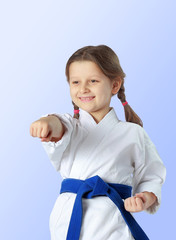 Cheerful girl with a blue belt beat a blow hand