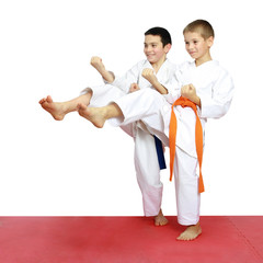 Cheerful boys athletes train beat blows kicks
