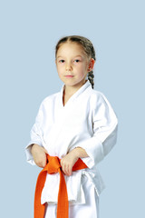 Athlete girl in a kimono with orange belt