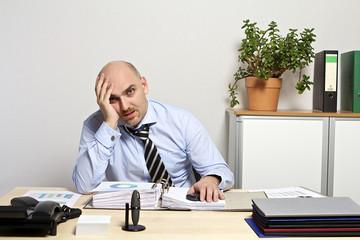 Geschäftsmann sitzt lustlos, und frustriert am Schreibtisch