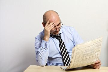 Mann sitzt am Tisch und liest eine Zeitung