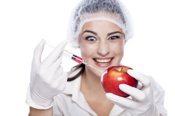 smiling malicious chemist woman injected some liquid in apple