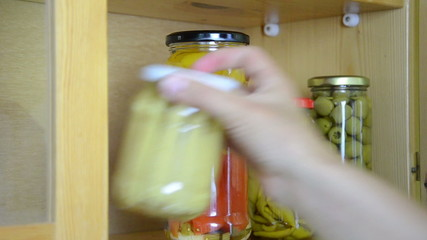 hand puts jars marinated olives hot pepper red yellow pepper